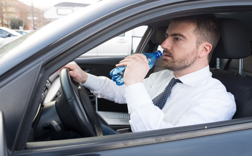 Kierowca pijący wodę w samochodzie